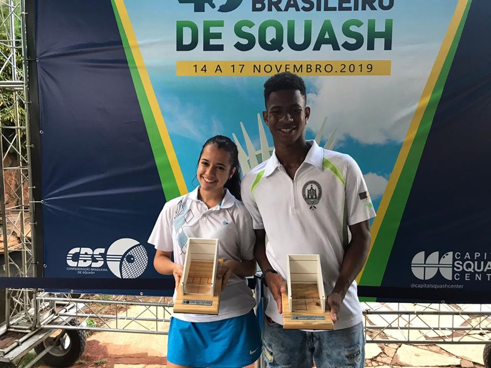 Squashinhos Emanuelle Nunes and João Victor holding their trophies from the Brazilian Squash Championship